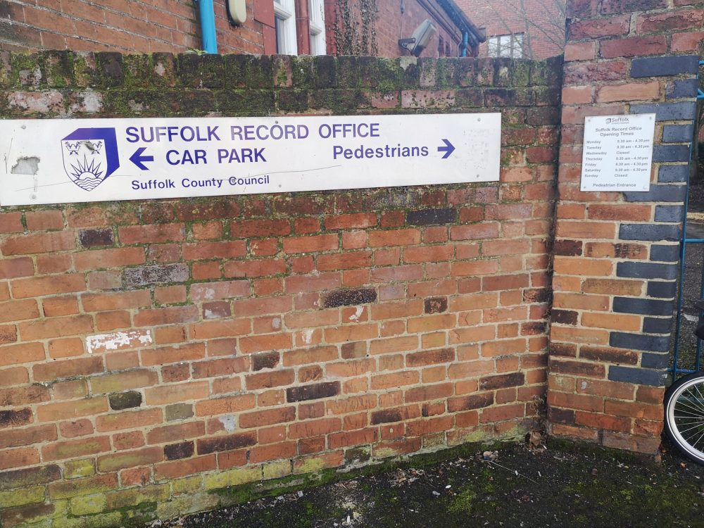 Entrance to Suffolk Record Office sign on brick wall